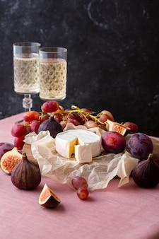 Brie su carta pergamena con fichi, prugne e uva e champagne sullo sfondo