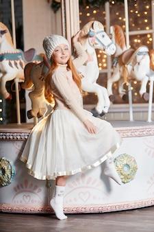 Brillante bambina dai capelli rossi in un cappello bianco