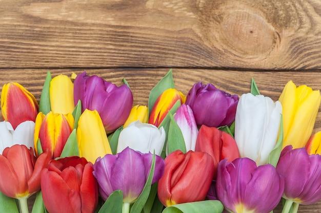Brillante primavera tulipani multicolore grande bracciata nella parte inferiore dello schermo su uno sfondo di legno chiaro.