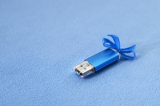 Brillante scheda di memoria flash usb blu con un fiocco blu si trova su una coperta di morbido tessuto felpato blu chiaro.