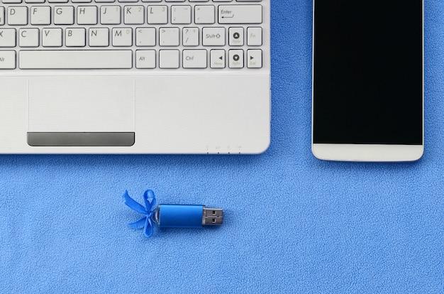 Brillante scheda di memoria flash usb blu con un fiocco blu si trova su una coperta