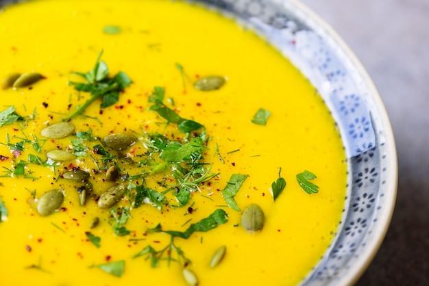 Brillante zucca biologica, lenticchie e zuppa di carote con semi ed erbe su grigio chiaro. copia spazio, vista dall'alto