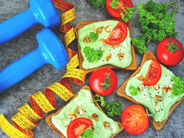 Brindare con ricotta verde, noci e pomodoro. nastro di misurazione. manubri. cibo fitness.