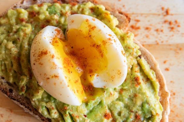 Brindisi di avocado con uovo sul tagliere