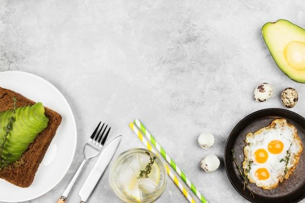 Brindisi di pane di segale con avocado, uova fritte di uova di quaglia, limonata su uno sfondo chiaro