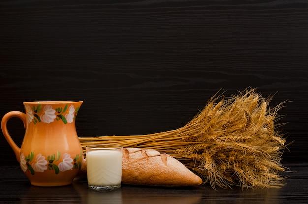 Brocca di argilla, un bicchiere di latte, pane di segale e un covone su sfondo nero