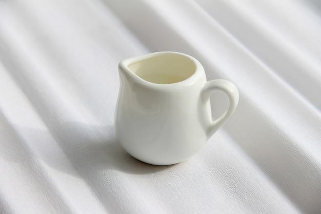 Brocca di latte con latte su una priorità bassa bianca