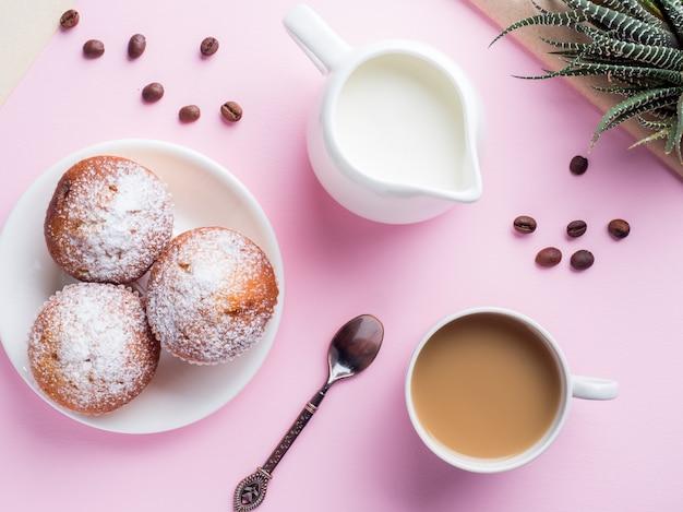 Brocca di latte del caffè dei muffin della prima colazione su un fondo rosa. vista dall'alto piatto posare.