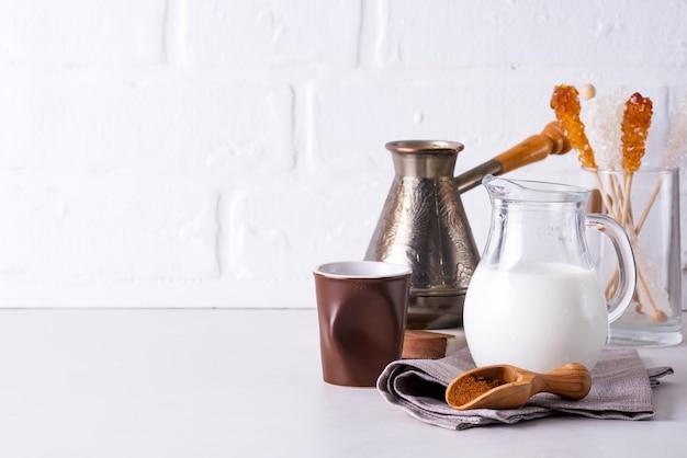 Brocca di latte e caffè macinato per fare un drink a casa su un piano di lavoro in pietra contro un muro bianco della cucina