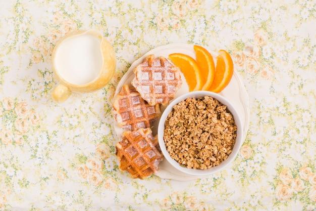 Brocca di latte e piatto di ciotola di muesli sano con cialde e fetta di arance