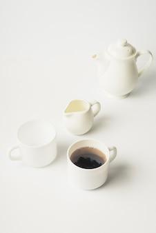 Brocca di latte; tazza di tè; tazza di ceramica e teiera su sfondo bianco