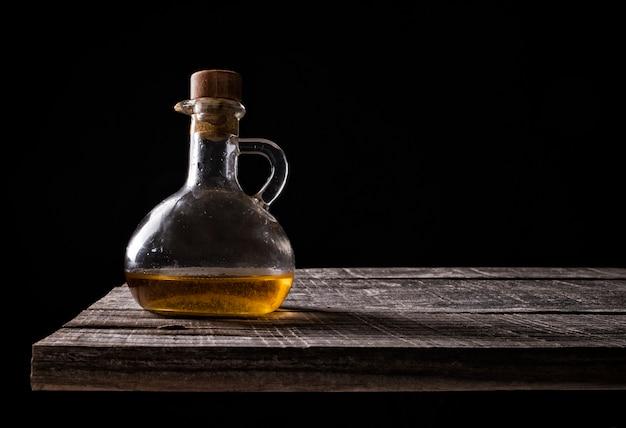 Brocca di olio d'oliva su legno vecchio su sfondo nero