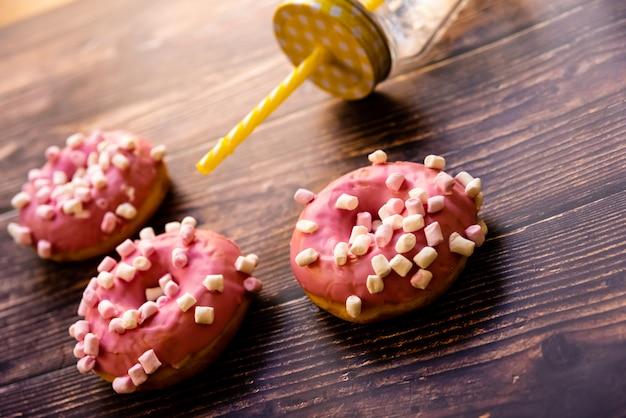 Brocca di succo con paglia colorata e ciambelle smaltate rosa su tavola di legno.
