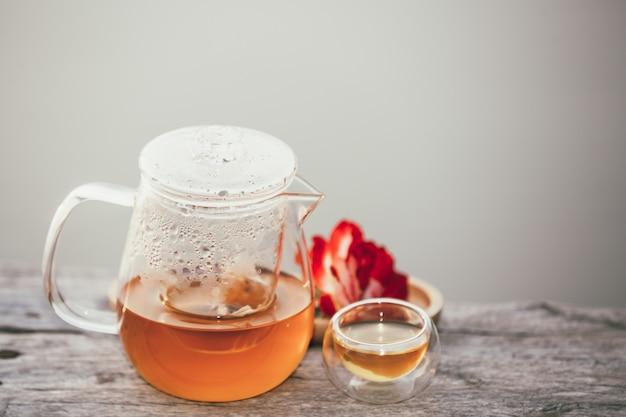 Brocca e bicchiere pieno di tè caldo