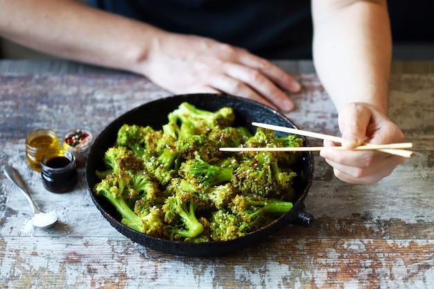 Broccoli cotti in padella. cibo sano. un uomo con le bacchette mangia broccoli.
