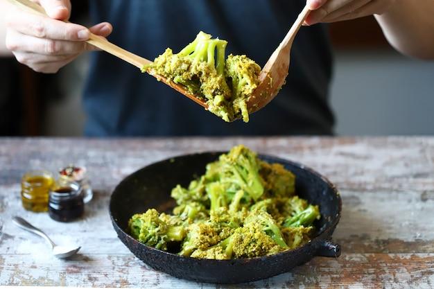Broccoli cotti in padella. lo chef mescola broccoli. cibo sano.
