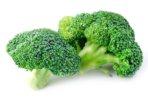Broccoli crudi freschi su un fondo bianco, vista laterale.
