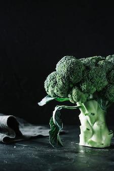 Broccoli del primo piano su fondo e sul panno neri