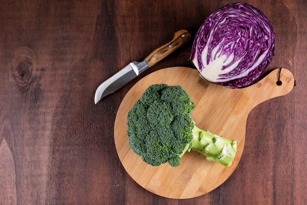 Broccoli di vista superiore sul bordo di legno con cavolo rosso