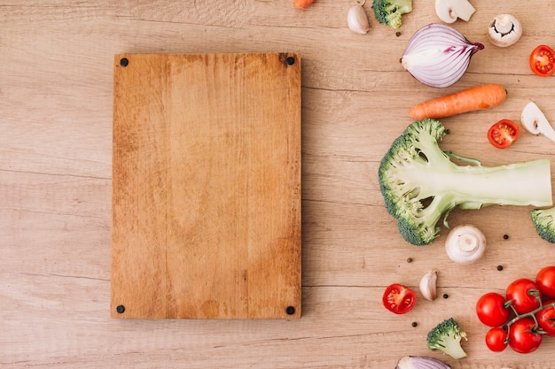 Broccoli divisi a metà; fungo; pomodori; carota vicino al tagliere sulla superficie in legno