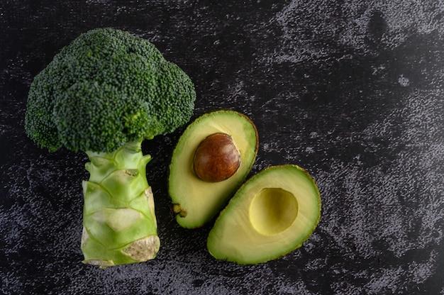 Broccoli e avocado su un pavimento di cemento nero.