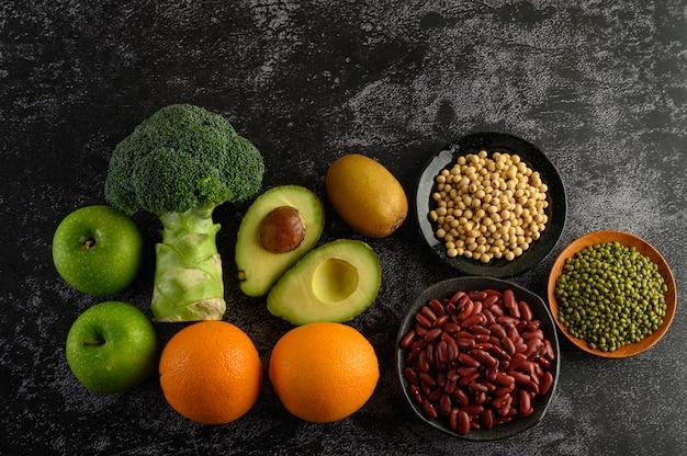 Broccoli, mela, arancia, kiwi, legumi e avocado su un pavimento di cemento nero.