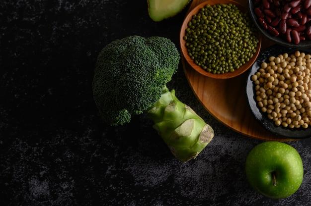 Broccoli, mela e legumi su un pavimento di cemento nero.