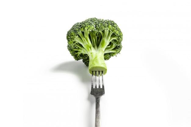 Broccoli su una forcella su un bianco