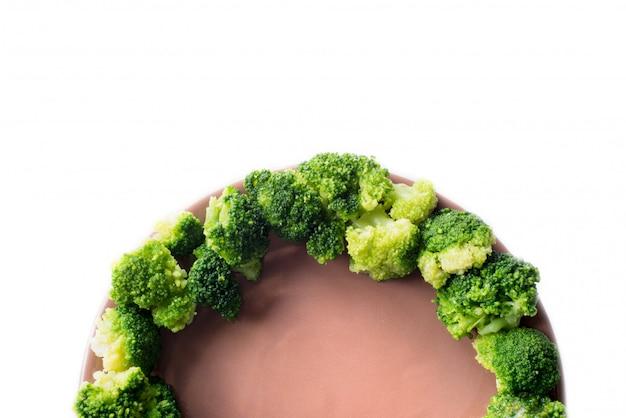 Broccoli sul piatto isolato su bianco