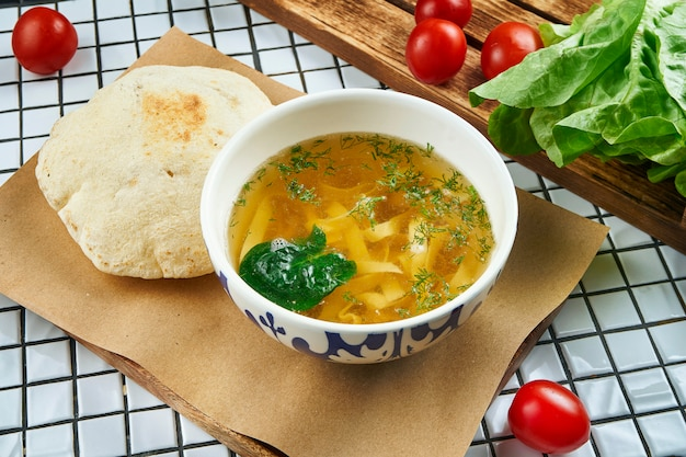 Brodo di pollo fatto in casa con pasta fatta a mano e verdure e focaccia panino sul tavolo bianco. cucina casalinga. vista da vicino