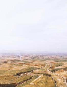 Brown e montagne verdi sotto il cielo bianco durante la nuova foto piacevolmente impressionante impressionante della natura di tempo