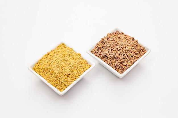 Brown e semi di lino dorati isolati su fondo bianco