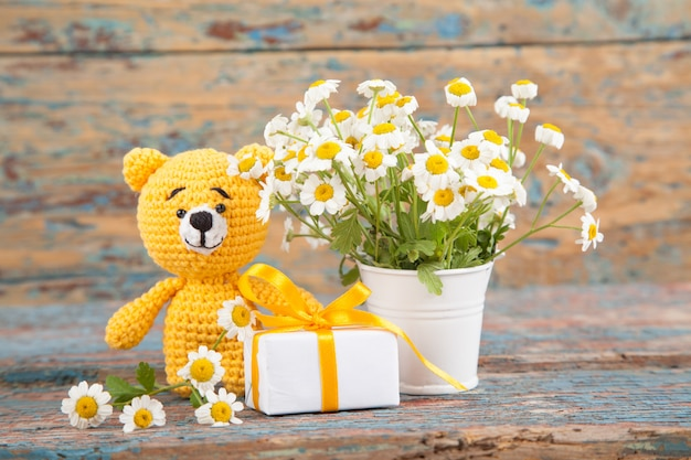 Brown ha lavorato a maglia l'orso piccolo con la camomilla su un vecchio fondo di legno. giocattolo lavorato a mano. amigurumi