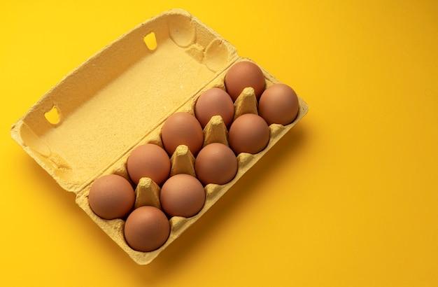 Brown uova di gallina in una scatola di cartone su sfondo giallo, vista dall'alto