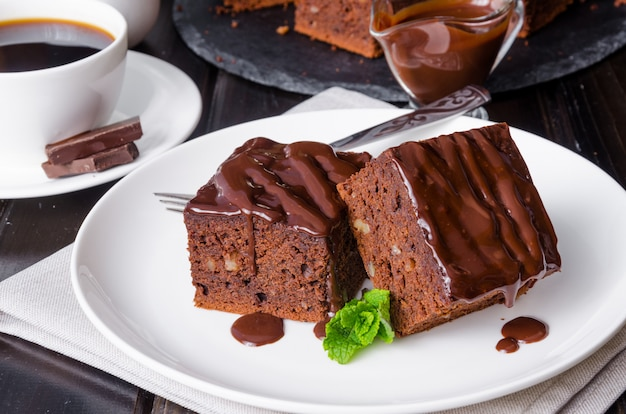 Brownie al cioccolato con noci e glassa su fondo di legno scuro