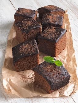 Brownie classici appena sfornati su pergamena sono disposti su un whi