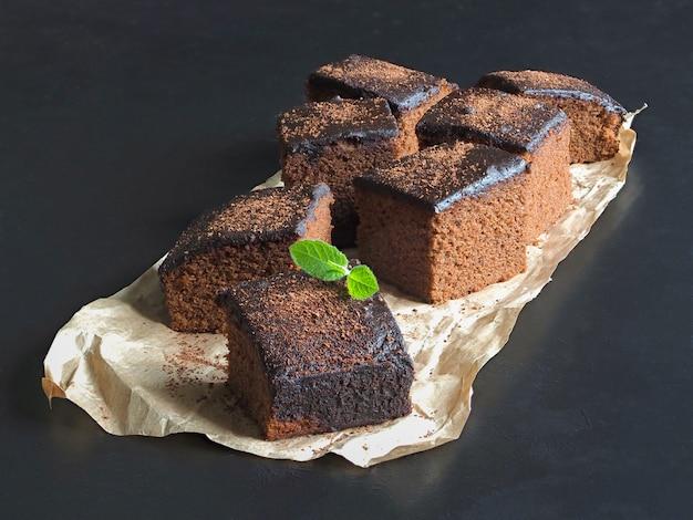 Brownie classici appena sfornati su pergamena sono disposti su una superficie nera