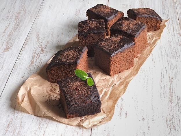 Brownie classico appena sfornato su pergamena sono disposti su un tavolo bianco