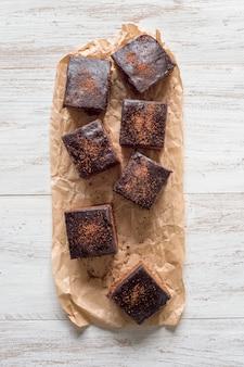 Brownie classico appena sfornato su pergamena sono disposti su una superficie di legno bianca
