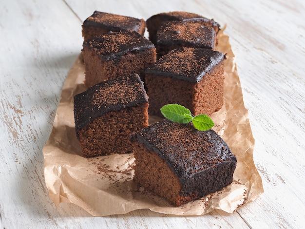 Brownie classico appena sfornato su pergamena sono disposti su una superficie di legno bianca.