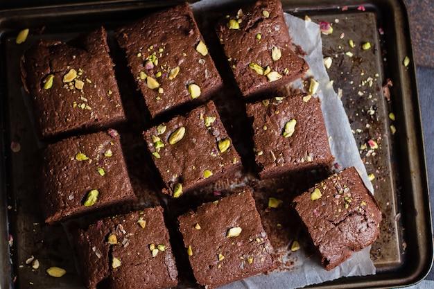 Brownies al cioccolato fatti in casa con pistacchi su sfondo scuro. copia spazio, vista dall'alto