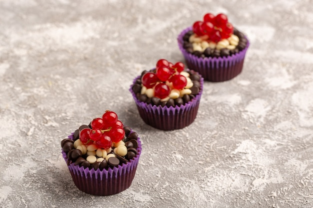 Brownies al cioccolato rivestiti in vista frontale con panna e gocce di cioccolato