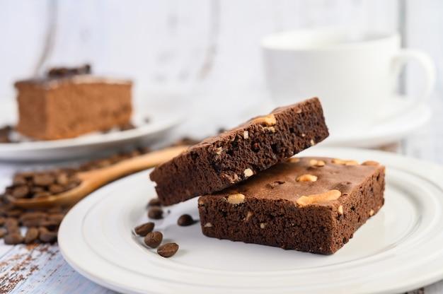 Brownies al cioccolato su un piatto bianco e chicchi di caffè su un cucchiaio di legno.