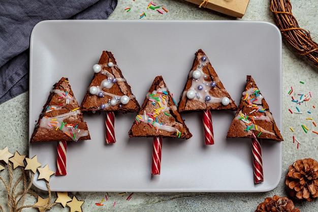Brownies dell'albero di natale con il bastoncino di zucchero e la glassa, fondo grigio, vista superiore. concetto di cibo di natale.