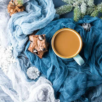 Brownies di crema di formaggio con biscotti sul blu e tazza di caffè e latte.