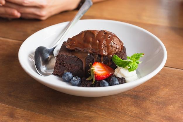 Brownies fatti in casa al cioccolato fondente conditi con frutta fresca.