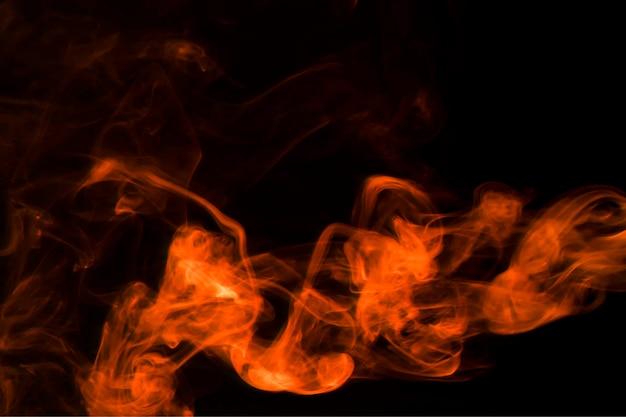 Brucia il fumo rosso astratto su sfondo nero