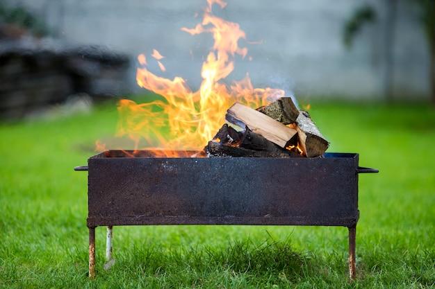 Bruciando brillantemente in legna da ardere scatola di metallo per barbecue all'aperto.