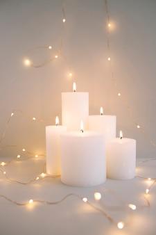 Bruciare candele bianche circondate da luci fata illuminate su sfondo grigio