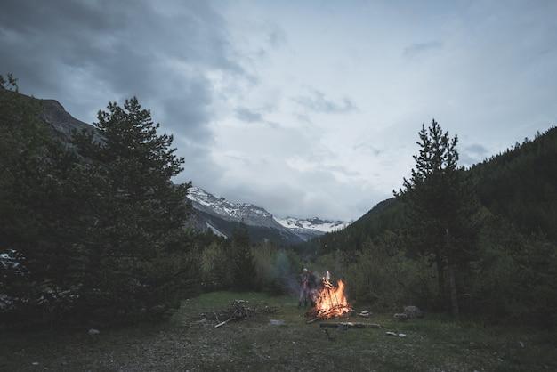 Bruciare il fuoco dell'accampamento nel bosco di larici e pini remoti
